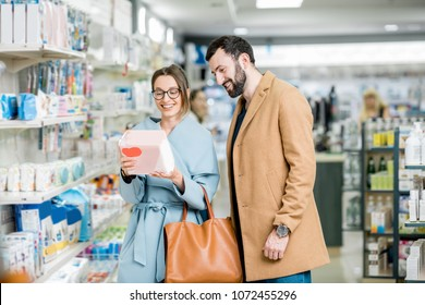 Young couple choosing diapers for baby standing in the pharmacy store