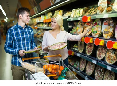 Young couple choosing Italian pizza in cooled food section and smiling