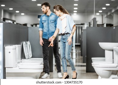 Young couple choosing lavatory pan standing together in the building shop with sanitary ceramics