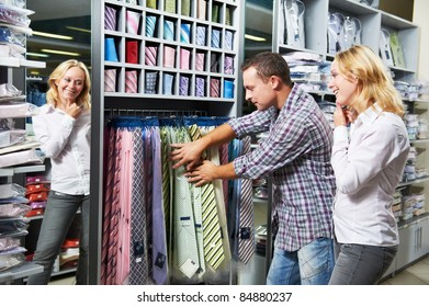 Young couple choosing necktie during clothes shopping at sales store