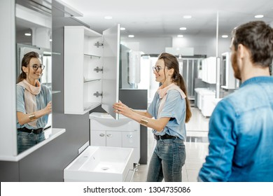 Young couple choosing new bathroom furniture at the plumbing shop with lots of sanitary goods