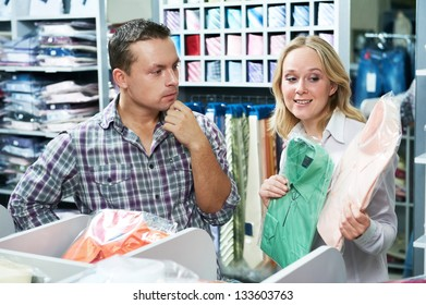 Young couple choosing shirt and necktie during clothes shopping at sales store