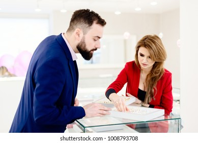 Young couple choosing wedding ring in jewelry store. Wedding decisions. Buying a present. Jewelry store. Attractive man with a beard choosing a ring gift in jewelry store