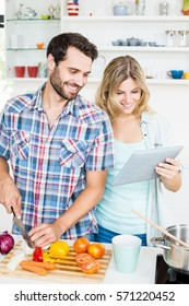 Young couple chopping vegetable and using digital tablet in the kitchen