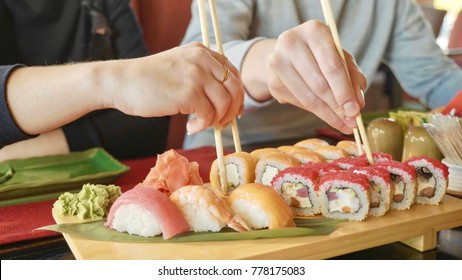 Young couple with chopsticks takes sushi from a plate in a japanese restaurant. Men and women starts eats japanese food. Focus on the seafood plate, close-up.