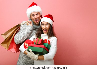 Young couple with Christmas purchases on pink background