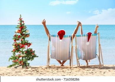 Young couple and Christmas tree on beach