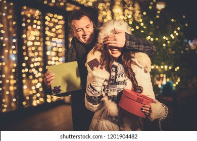 Young couple in the city centre with holiday's brights in background. Smiling man covering the eyes of happy surprised girlfriend in a Christmas night.