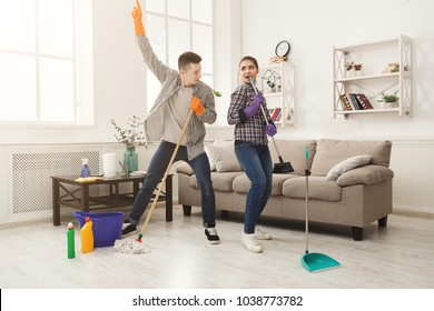 Young couple cleaning home, playing with mop and broom, having fun in living-room. Housekeeping and home cleaning concept