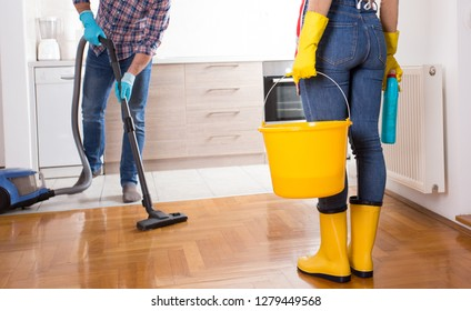 Young couple cleaning home together. Man hoovering and girl holding bucket for mopping floor
