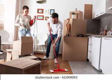 Young couple cleaning and selecting things at they new home.Moving house.