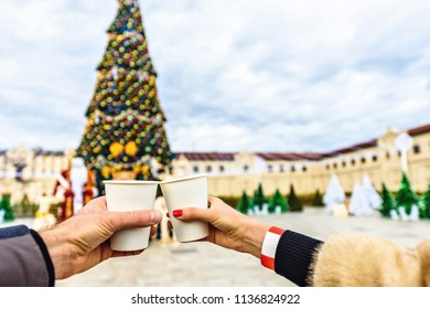 Young couple clinking coffee cups at Mimi Castle. Christmas tree on background. Cloudy sky on background. Negative copy space, place for text. Bulboaca, Anenii Noi, Moldova