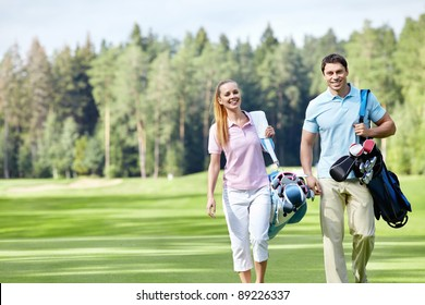 Young couple with clubs on the golf course