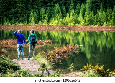 Young couple in colorful sweatshirts is standing in front of the volcanic lake on Azores Islands. Beautiful reflections on the background and beautiful green forest. Portugal.