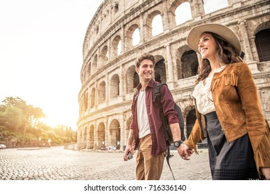 Young couple at the Colosseum, Rome - Happy tourists visiting italian famous landmarks