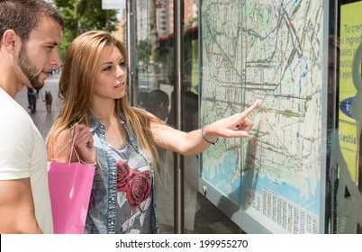 Young couple consulting a map in the city of Barcelona
