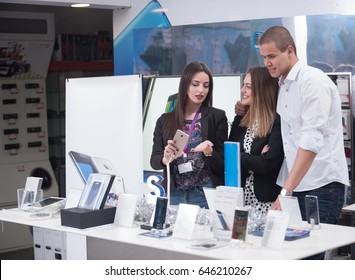 Young couple in consumer electronics store looking at latest laptop, television,mobile and photo camera
