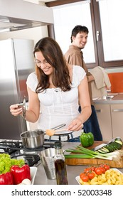 Young couple cook in modern kitchen, man helping with dishes