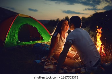 A young couple is cooking bread on a fire at night