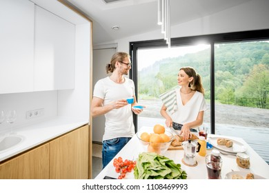 Young couple cooking breakfast with healthy food and coffee standing at the modern kitchen interior with big window and green area outdoors