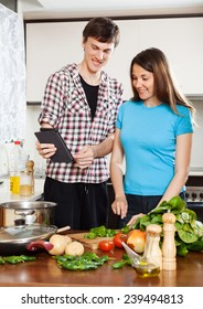 Young couple cooking with eBook in home kitchen
