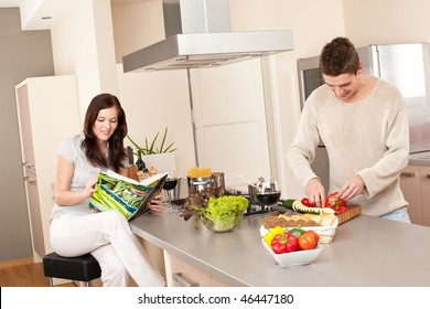Young couple cooking in kitchen together with cookbook