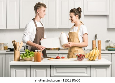 young couple cooking salad and holding paper towel in kitchen