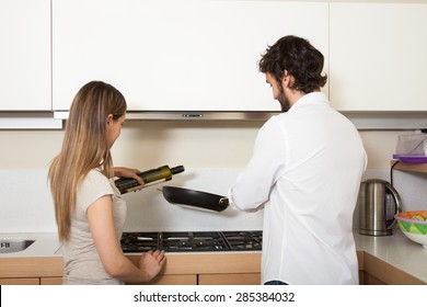 Young couple cooking in their kitchen