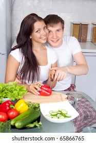 young couple cooking together in the kitchen at home (focus on the man)