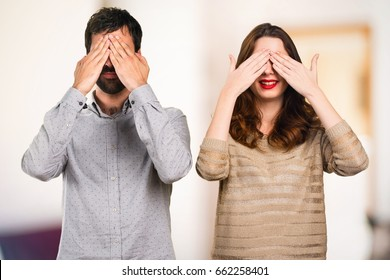 Young couple covering their eyes on unfocused background