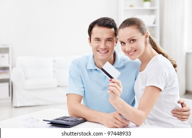 A young couple with a credit card at home