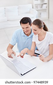 A young couple with a credit card in the laptop looks