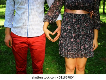 Young couple crossed her arms in the form of heart