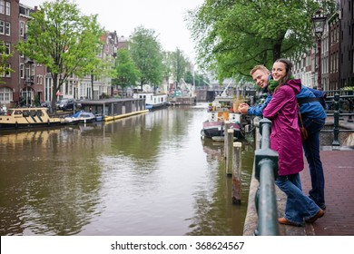 Young couple Cucazian enjoy the beauty of Amsterdam, even if it rains