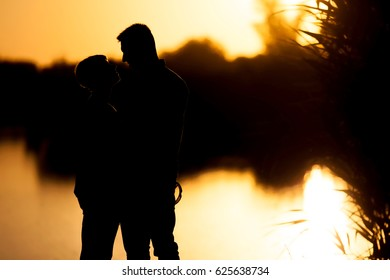 Young couple cuddle in sunset