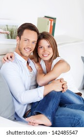 Young couple cuddling on couch in the living room