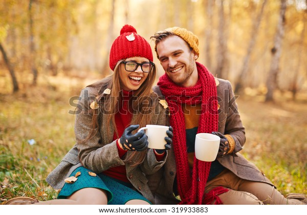 Young couple with cups of tea spending leisure in park