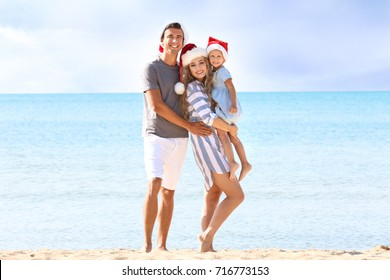 Young couple with cute girl on beach. Christmas celebration concept