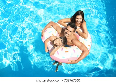 Young couple and cute son with inflatable ring in pool