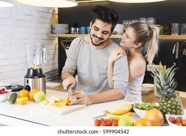 Young couple cutting fruit in the kitchen