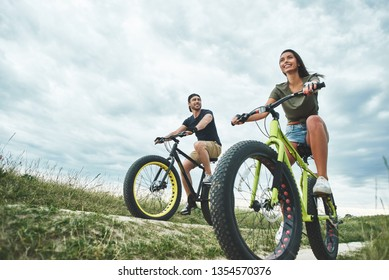 Young couple are cyclingat green hills . Front view