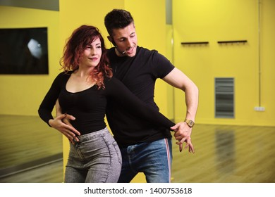 A young couple of dance instructors teaching salsa and bachata