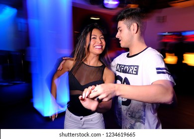 a young couple dancing bachata and salsa at the disco