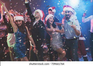 Young couple dancing with glasses of champagne in hands. Behind them dance their friends and a man dressed as Santa Claus. Against the background of colored smoke, confetti flies around.