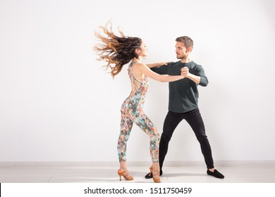 Young couple dancing latin dance bachata, merengue, salsa, kizomba. Two elegance pose over white background with copy space