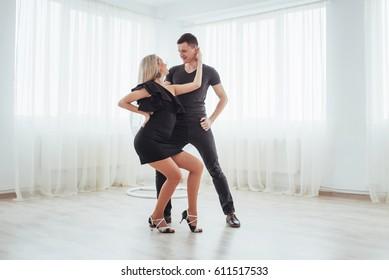 Young couple dancing latin music: Bachata, merengue, salsa. Two elegance pose on white room.