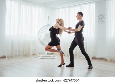 Young couple dancing latin music: Bachata, merengue, salsa. Two elegance pose on white room.