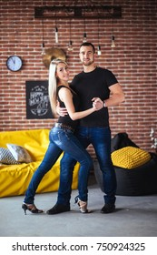 Young couple dancing latin music: Bachata, merengue, salsa. Two elegance pose on cafe with brick walls.