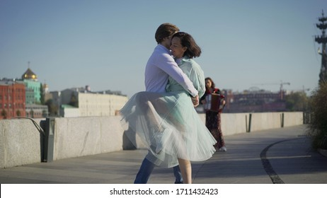 A young couple dancing to live music on the street. Musicians play, and a young couple dancing on the promenade. Music street performers couple with girl violinist and man guitarist on blue sky