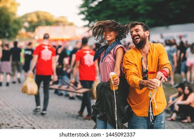 Young couple dancing at the music festival and spilling beer